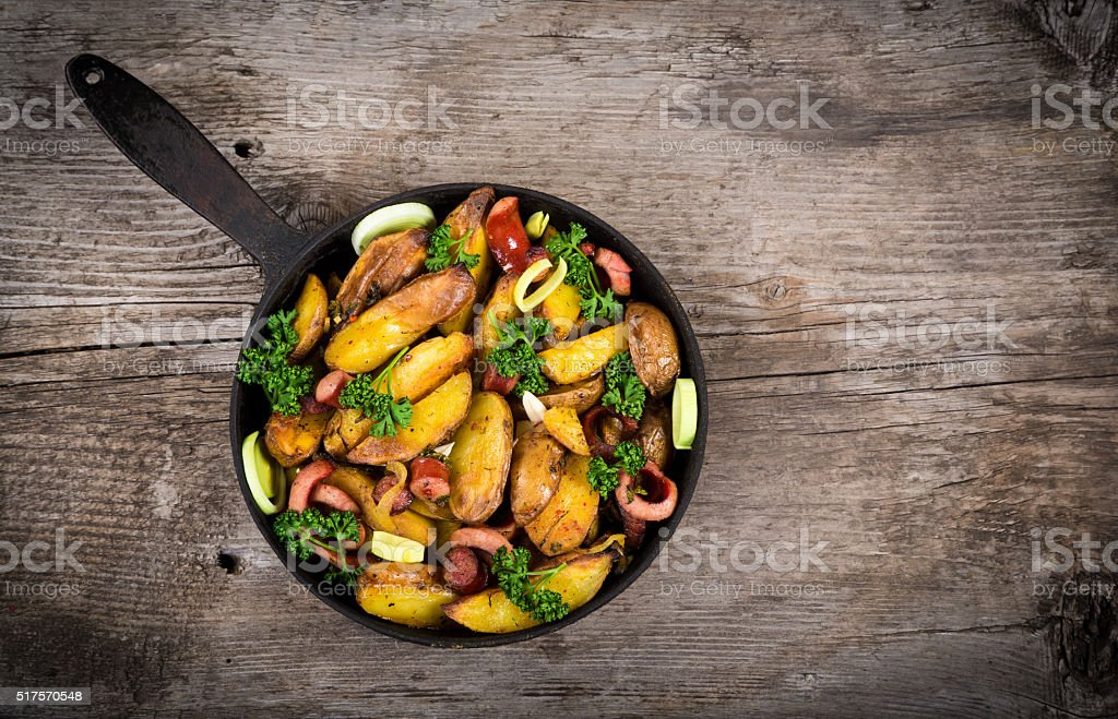 Fried potatoes with sausages on wooden table stock photo
