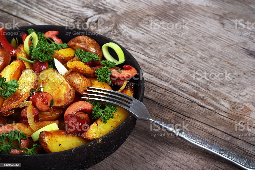 Fried potatoes with sausages, onion rings and green parsley. stock photo