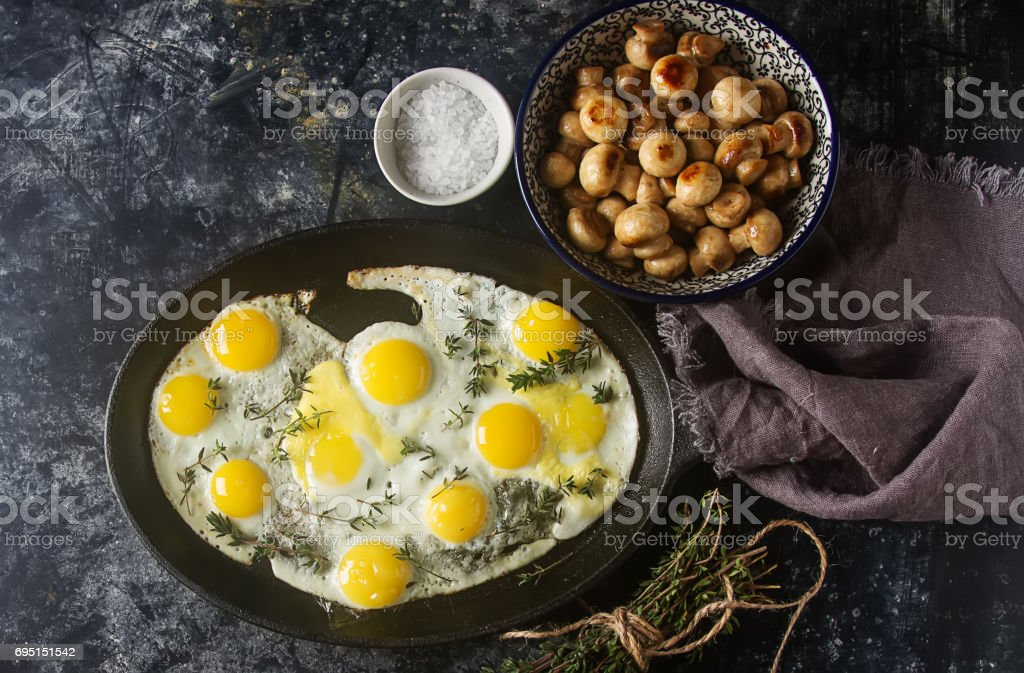 Fried quail eggs in a frying pan with thyme and mushrooms. Dark background. stock photo