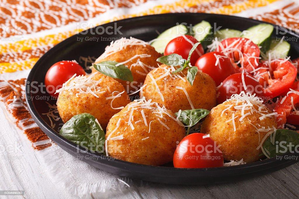 Fried rice balls and fresh vegetable salad on plate. horizontal stock photo