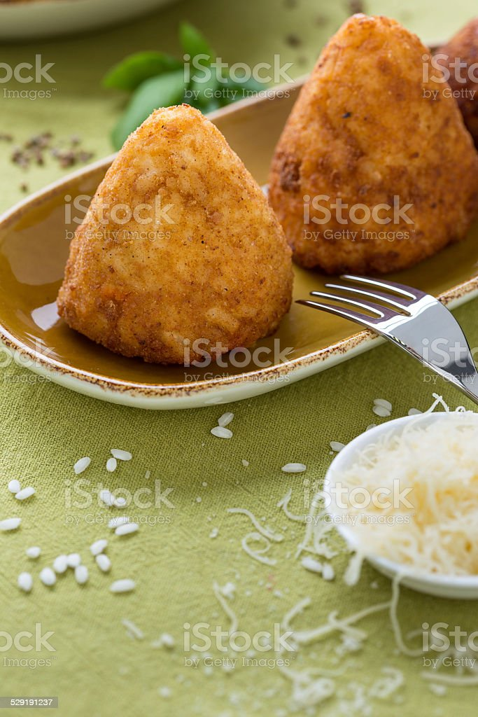 fried rice croquettes on brown plate with cheese and fork stock photo