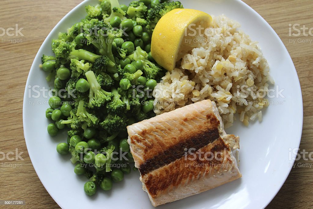 Fried salmon fillet, brown rice, peas, broccoli, healthy meal diet stock photo