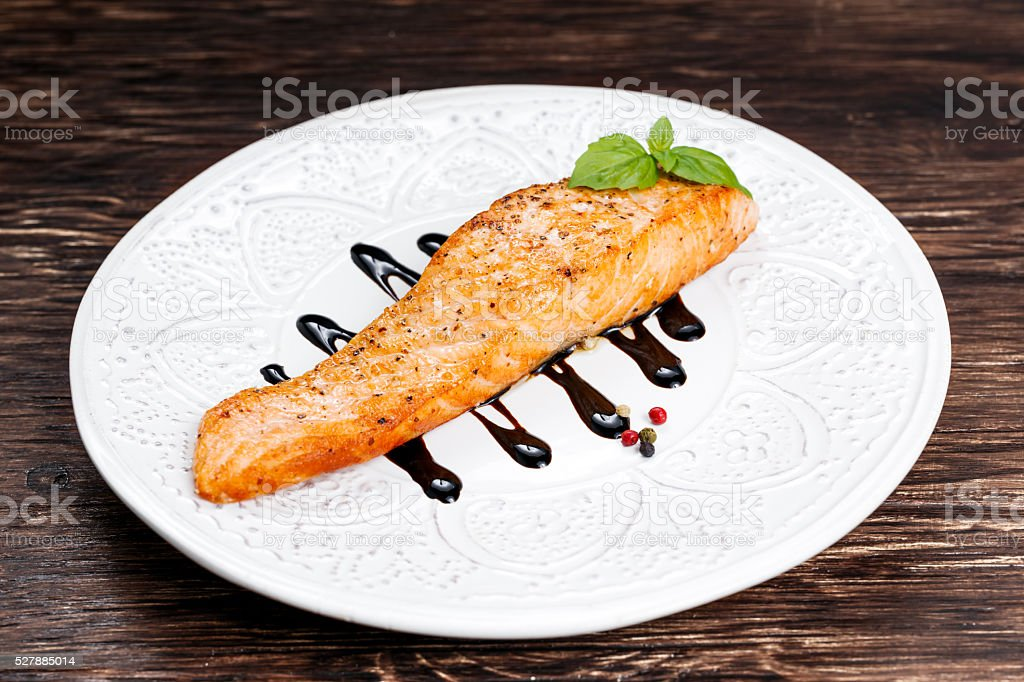 Fried salmon fillet served with reduced balsamic vinegar stock photo
