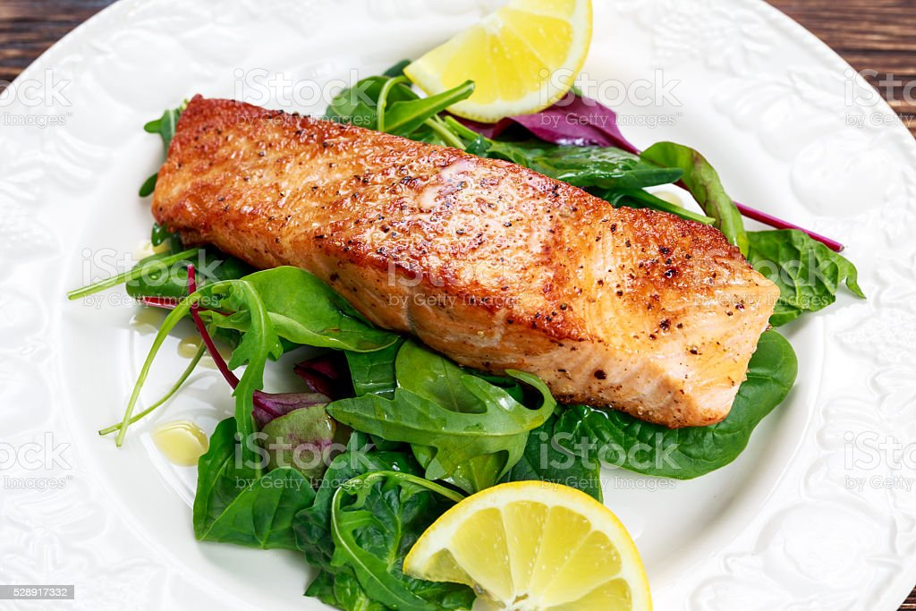 Fried salmon fillet served with vegetables and lemon stock photo