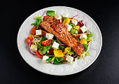 Fried Salmon steak with fresh vegetables salad. concept healthy food.