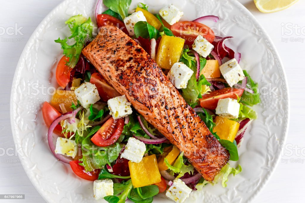 Fried Salmon steak with fresh vegetables salad, feta cheese. concept healthy food. stock photo