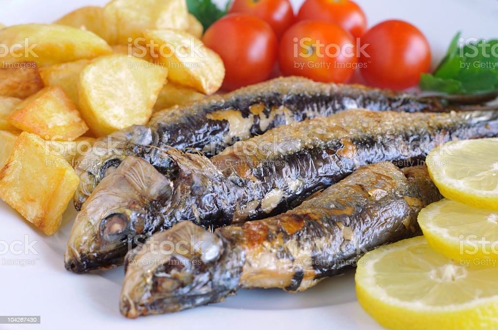 Fried sardines on the plate stock photo