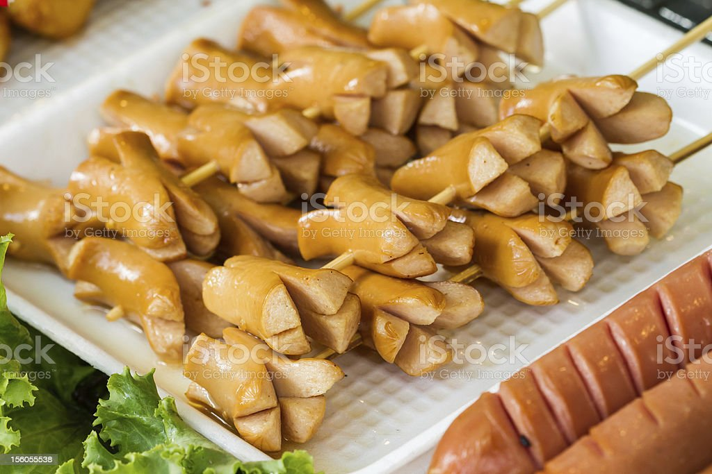 Fried sausage stick with wooden skewer royalty-free stock photo