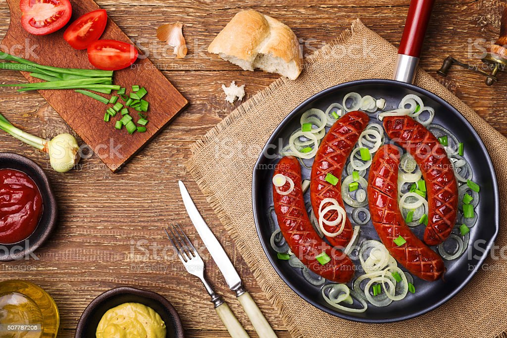 Fried sausages in a pan with onions. stock photo