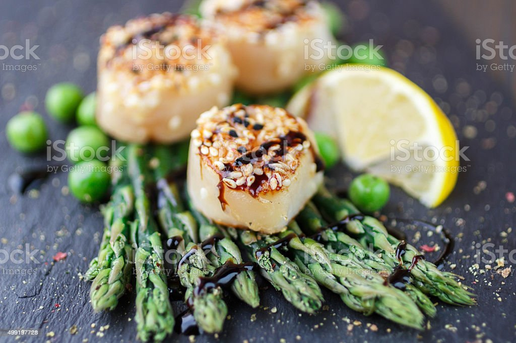 Fried scallop  with sesame seeds, balsamic sauce and asparagus royalty-free stock photo