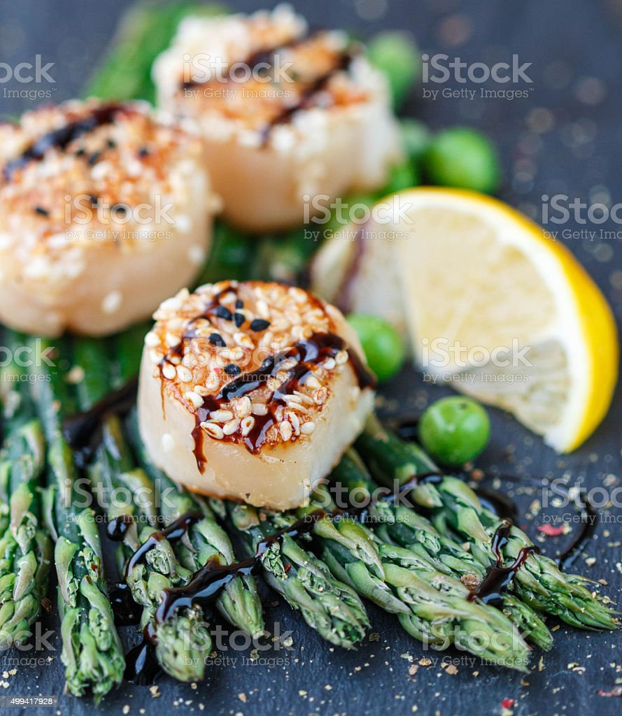 Fried scallop  with sesame seeds, balsamic sauce and asparagus stock photo