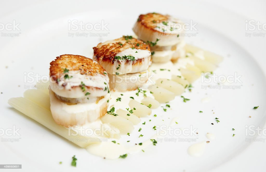 Fried scallops with asparagus and cream sauce stock photo
