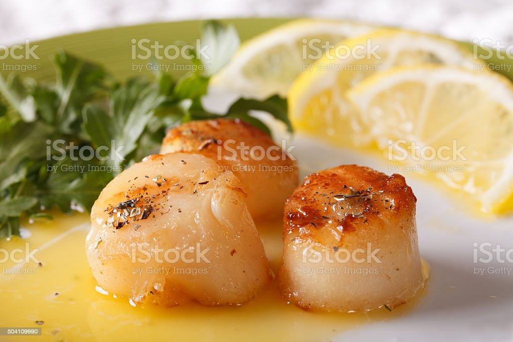 Fried scallops with sauce on a plate macro. horizontal stock photo