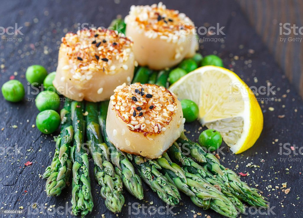 Fried scallops with sesame seeds, asparagus  and  lemon stock photo