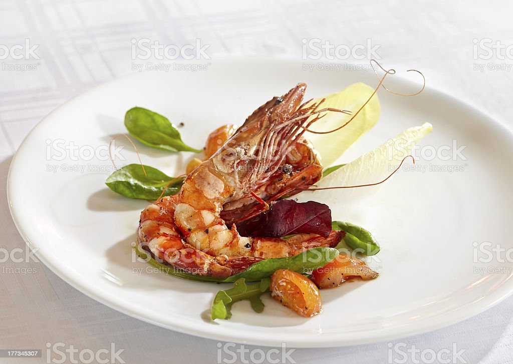 fried scampi with mixed salad leaves and cherry tomatoes stock photo