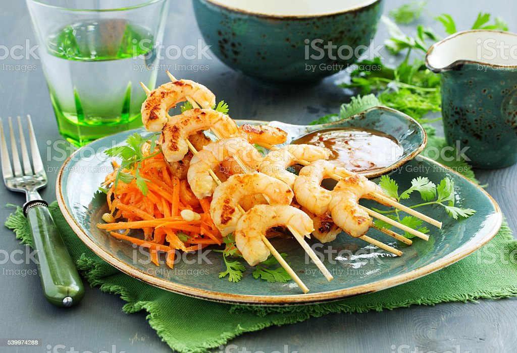 Fried shrimp on skewers with salad from carrots. stock photo