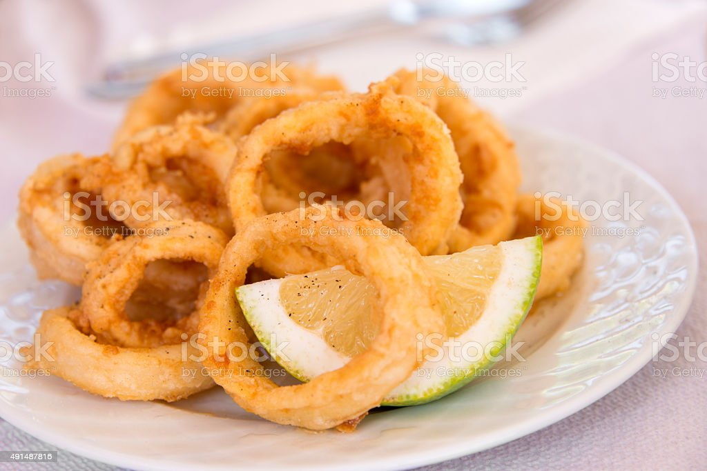 Fried squid rings with a slice of lemon stock photo