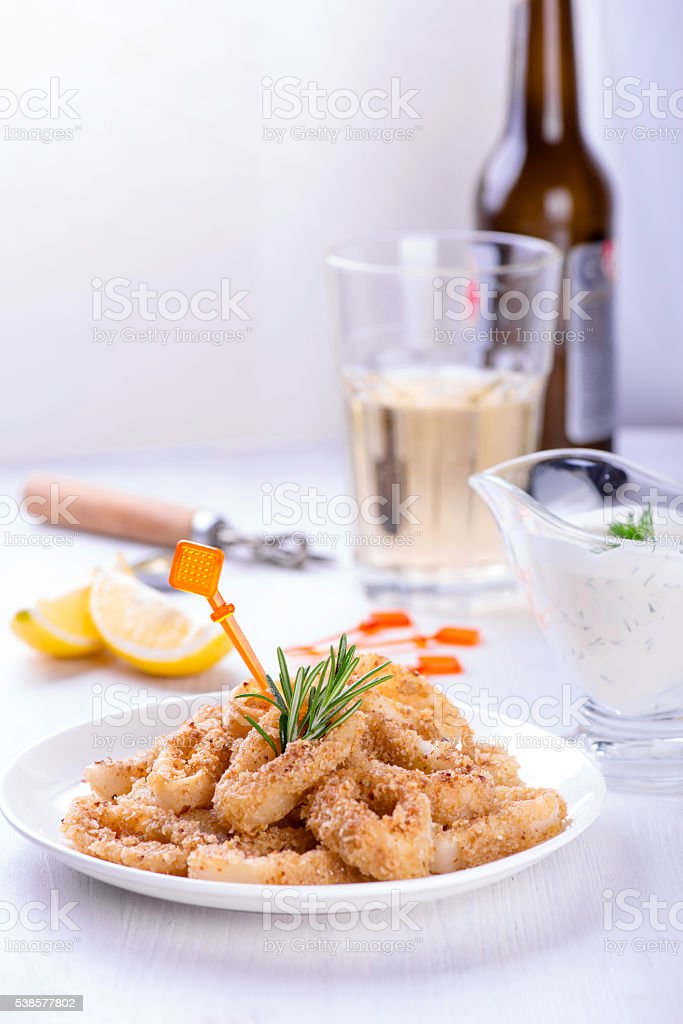 Fried squid rings with lemon, herbs and spices stock photo
