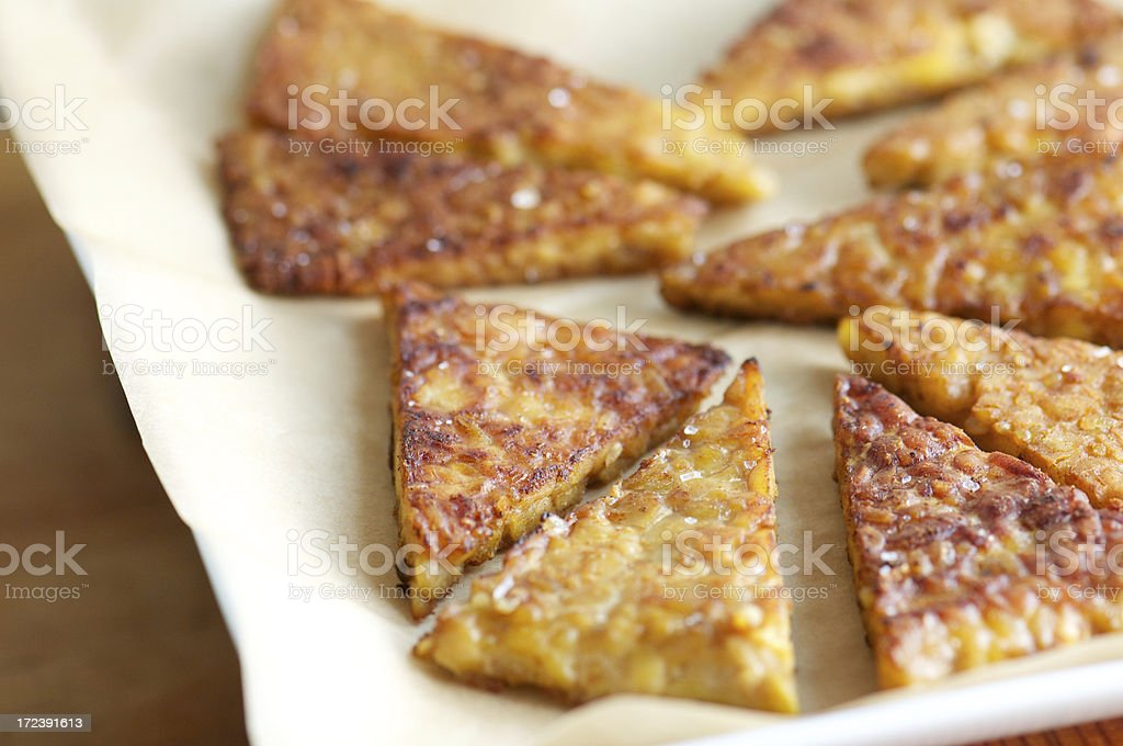 Fried Tempeh Triangles on Parchment Paper stock photo
