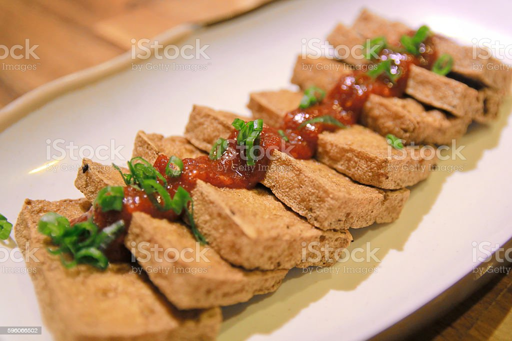 Fried Tofu topping chilli sauce and sliced onion leafs stock photo