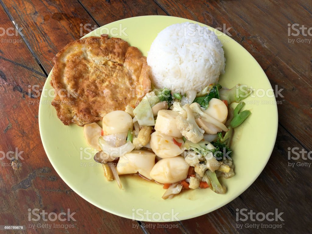 fried tofu with vegetables and Thai Omelette (scrambled eggs) in green dish on wooden table. Thai style Food. Vegetarian Food. vintage tone. stock photo