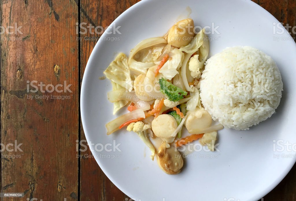 fried tofu with vegetables in white dish with thai jasmine rice on wooden background. Thai style Food. Vegetarian Food. stock photo