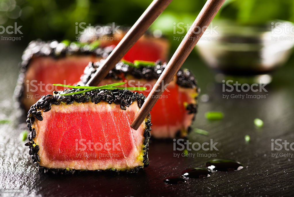 Fried tuna steak in black sesame with chopsticks stock photo