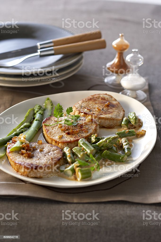 Fried veal with asparagus granada  on white plate stock photo
