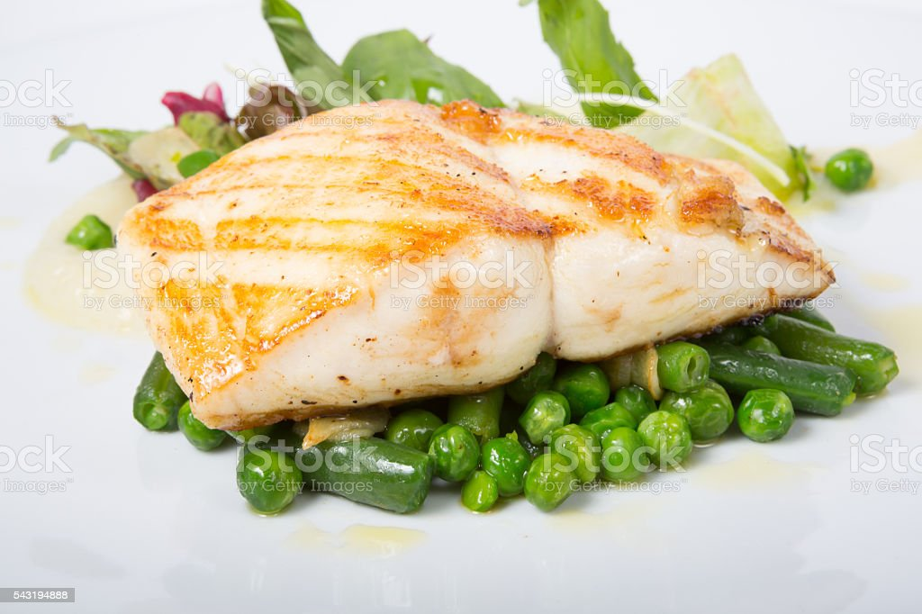 Fried white fish fillet with garnish stock photo