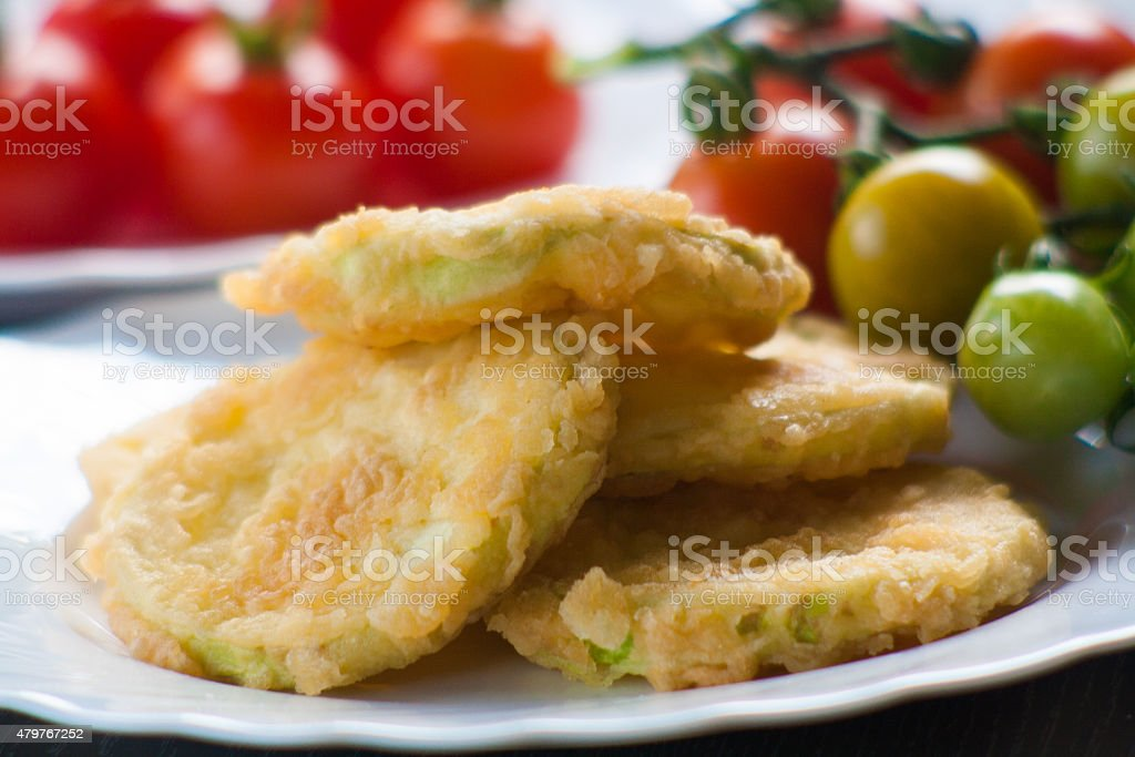Fried Zucchini and red cherry tomatoes stock photo
