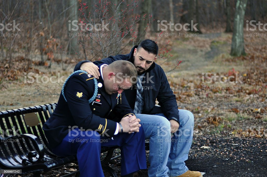Friend Comforts Uniformed Army Soldier stock photo