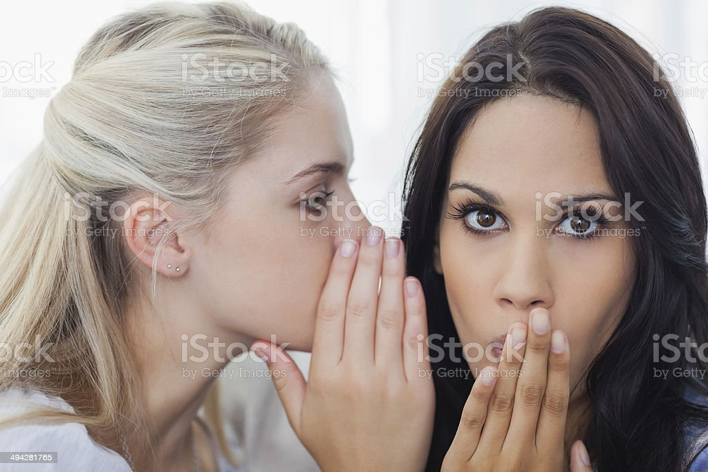Friend telling secret to brunette woman stock photo