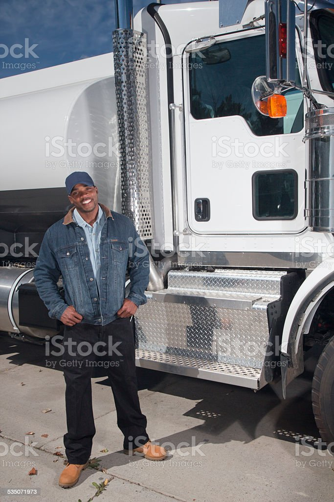 Friendly African American Trucker in Front of a Truck stock photo