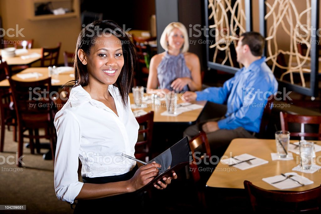 Friendly African-American waitress in restaurant taking customer orders royalty-free stock photo