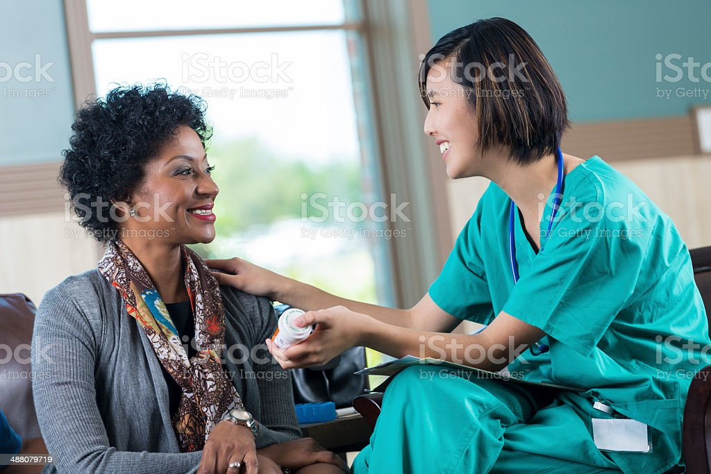 Friendly Asian nurse or doctor giving medication to patient stock photo