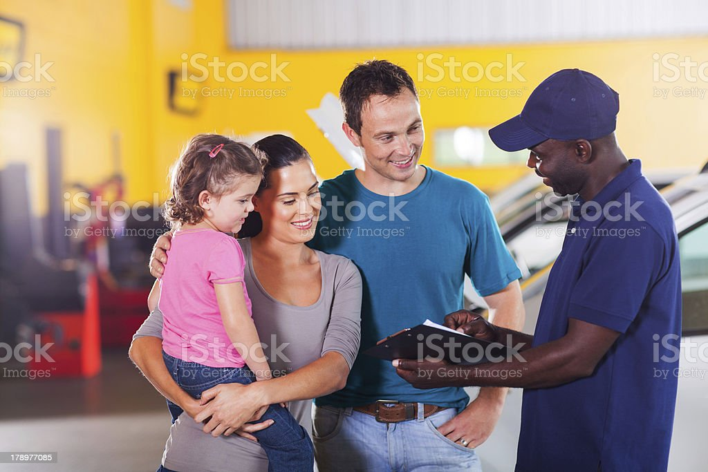 friendly auto mechanic talking to young family royalty-free stock photo