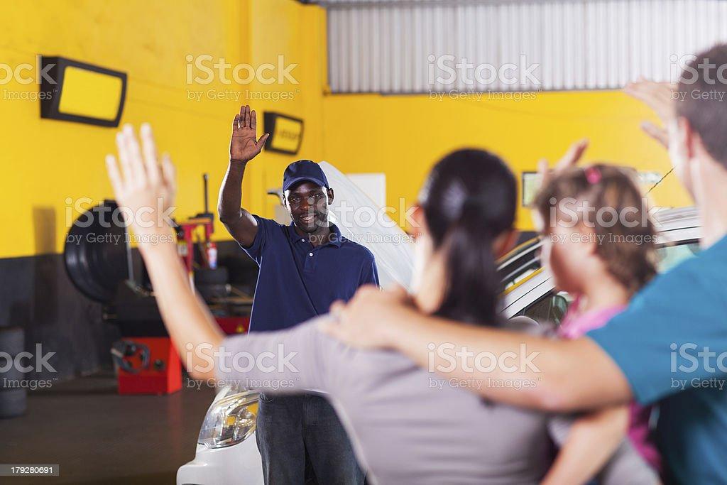 friendly auto repair shop worker waving good bye to customer royalty-free stock photo