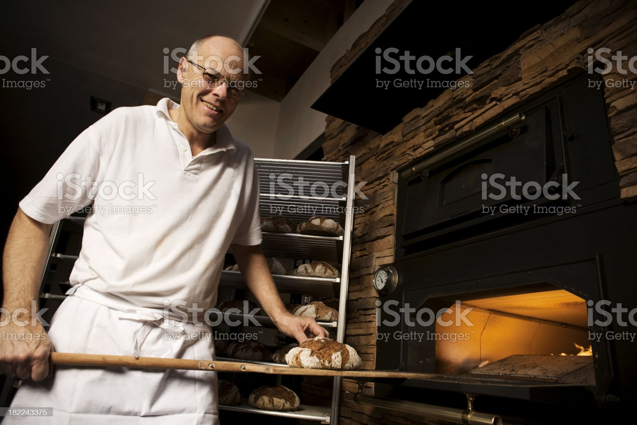 Friendly baker putting bread in oven royalty-free stock photo