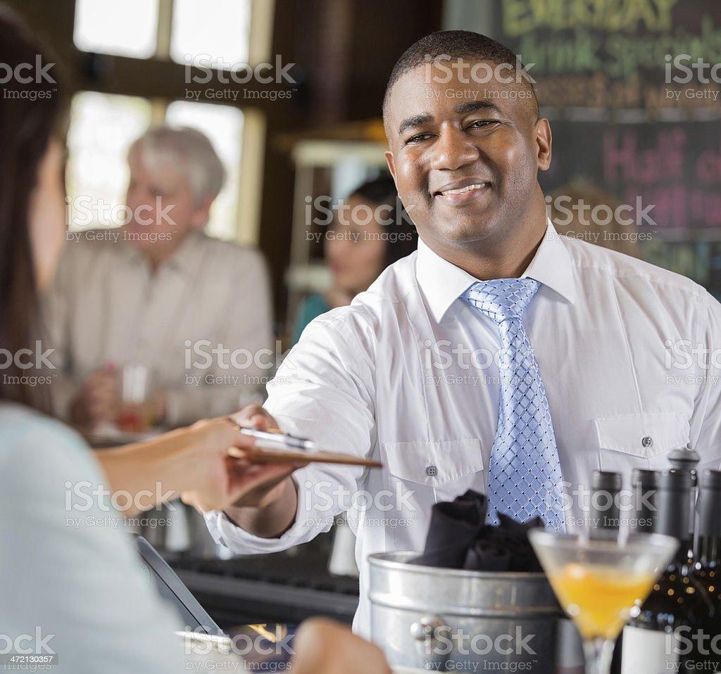 Friendly bartender giving customer check at restaurant bar stock photo