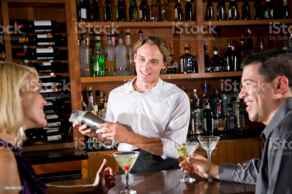 Friendly bartender mixing drink chatting with couple in restaurant bar royalty-free stock photo