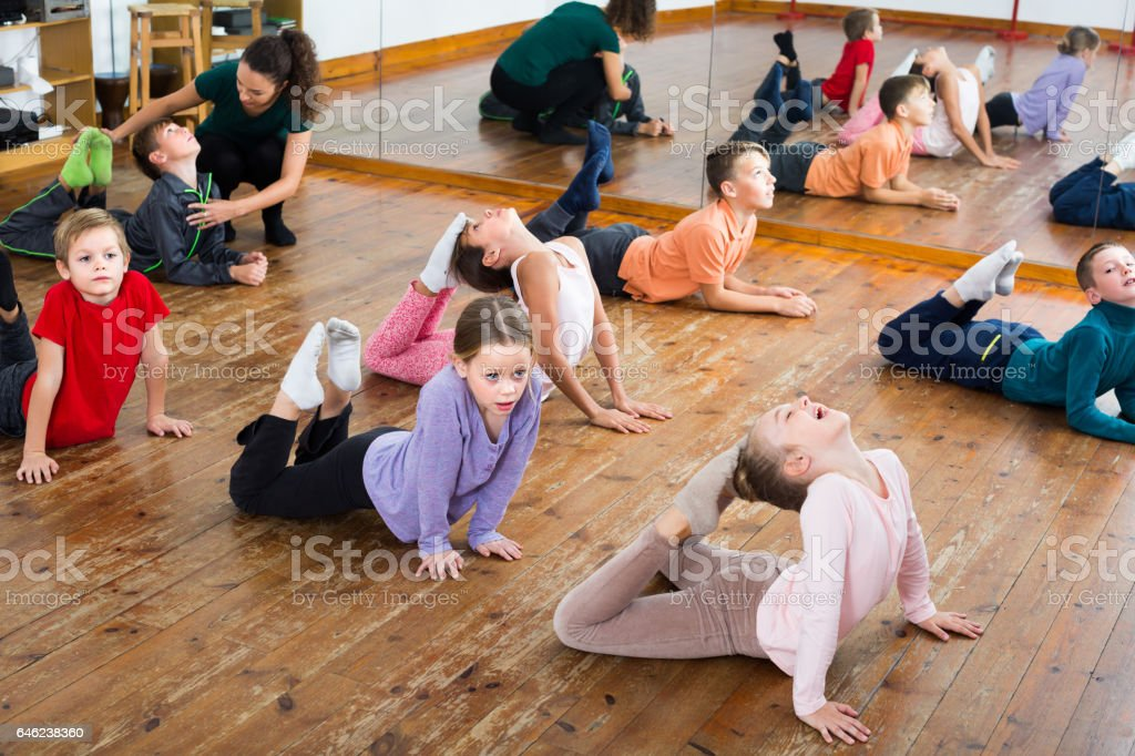 Friendly boys and girls with trainer stretching in dance hall