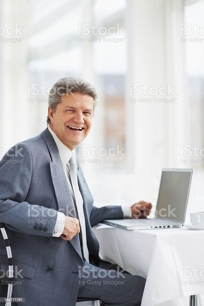 Friendly businessman sitting with his laptop royalty-free stock photo