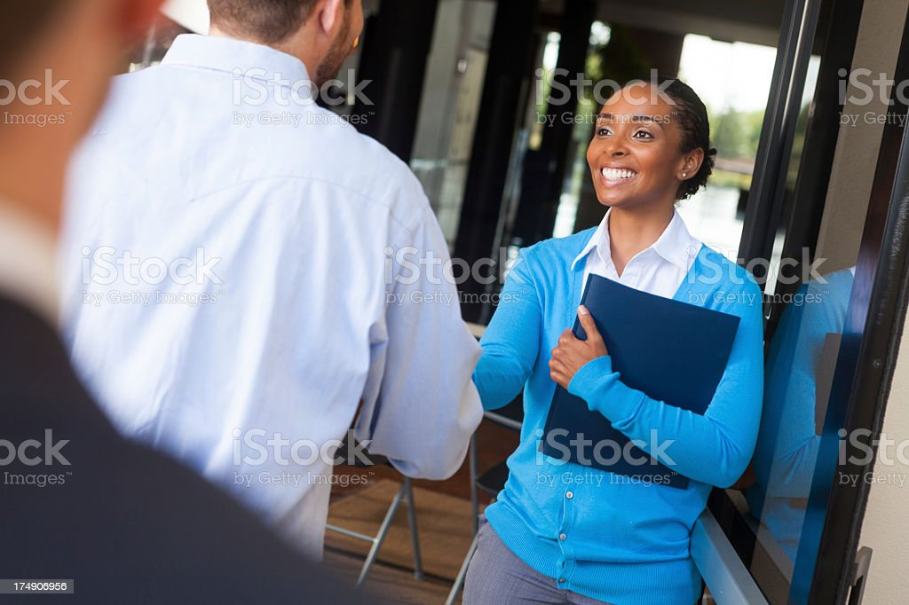 Friendly businesswoman shaking hands and greeting client in office doorway stock photo