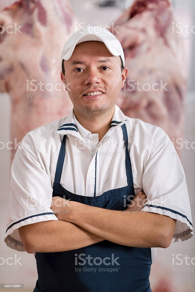 Friendly butcher smiling stock photo