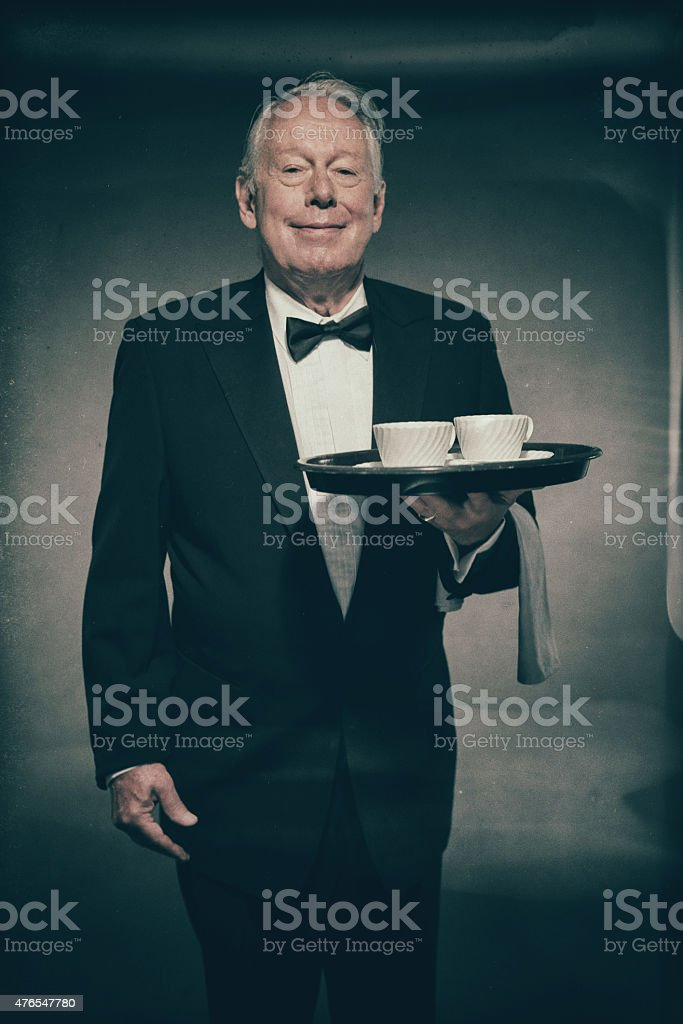 Friendly Butler Holding White Coffee Cups on Tray stock photo