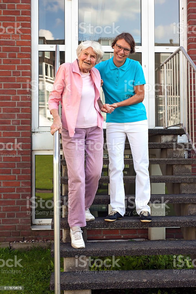 Friendly carer helping a senior lady on steps. stock photo