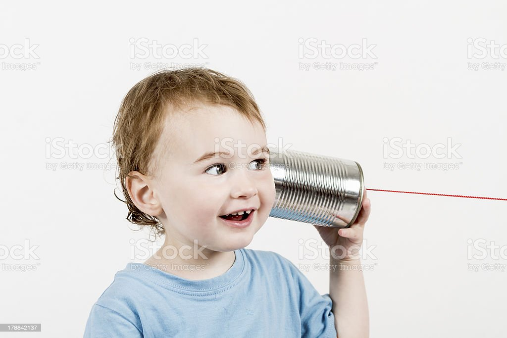 friendly child listening to tin can phone stock photo
