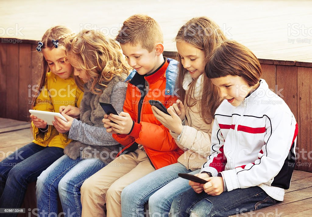 Friendly children sitting with mobile devices stock photo