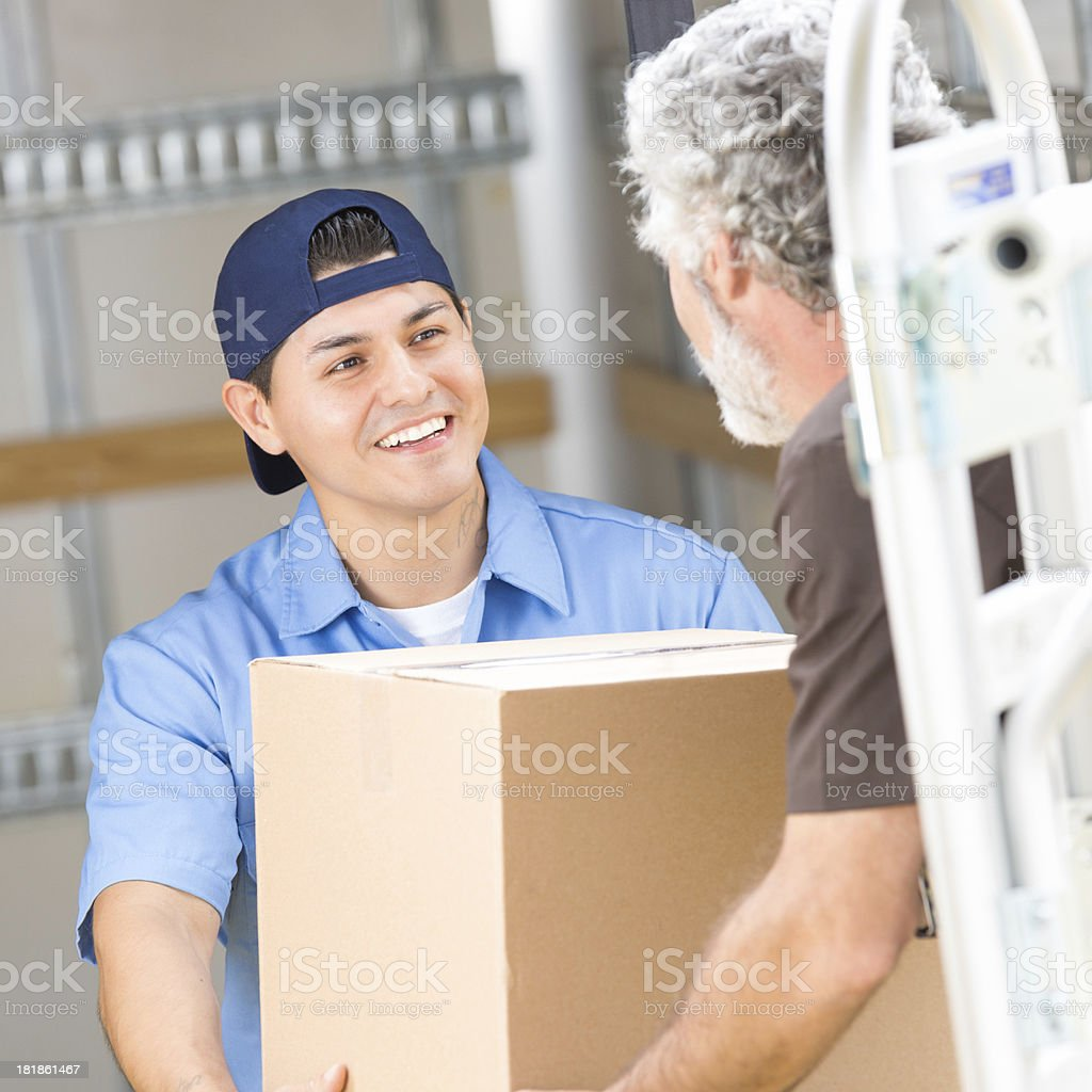 Friendly delivery driver delivering packages to warehouse royalty-free stock photo
