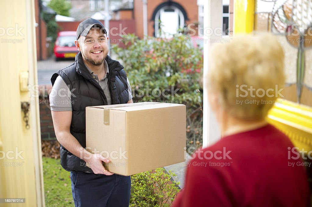 Friendly delivery man delivers parcel royalty-free stock photo